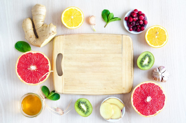 Bovenaanzicht helften van citrusvruchten en producten met vitamine c op lichte houten achtergrond