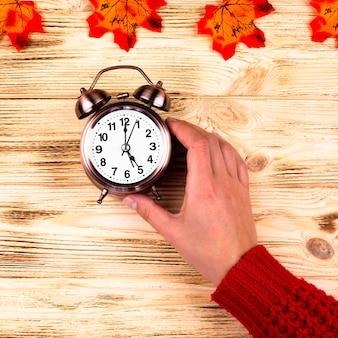 Bovenaanzicht herfstbladeren met klok