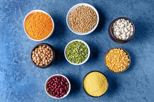 Bovenaanzicht het assortiment van erwten, linzen en peulvruchten op blauw.