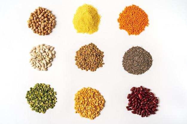 Bovenaanzicht het assortiment van erwten, linzen en peulvruchten op wit wordt geïsoleerd.