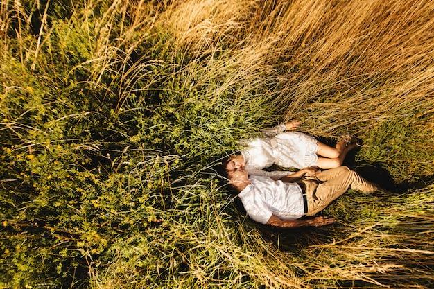 Bovenaanzicht het jonge paar dat in het gras ligt en geniet van aard