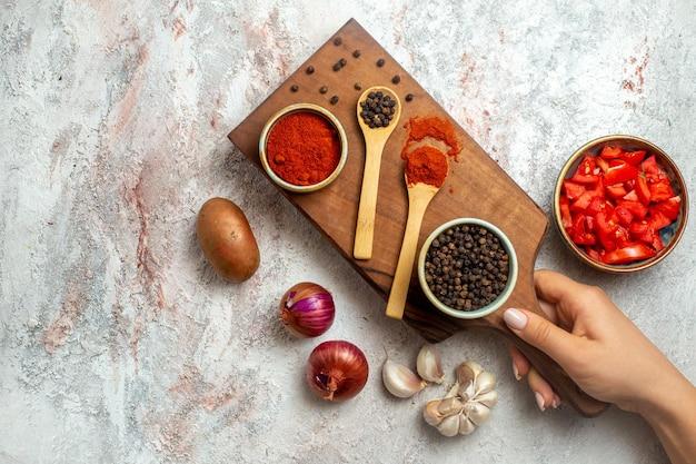 Bovenaanzicht hete peper met knoflook en tomaten op een witte ruimte