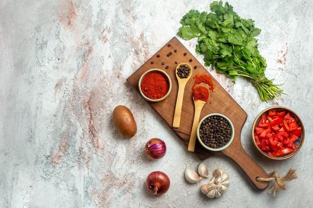 Bovenaanzicht hete peper met knoflookgroenten en tomaten op witruimte