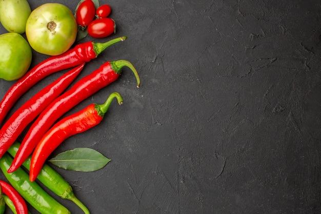 Bovenaanzicht hete rode en groene paprika's en tomaten laurierblaadjes aan de linkerkant van zwarte grond met vrije ruimte