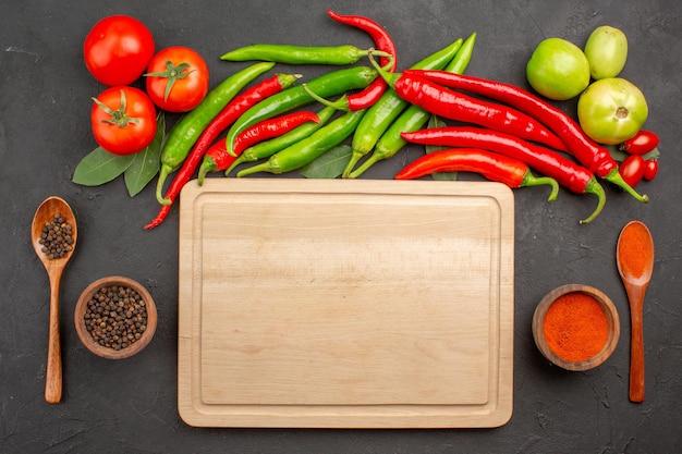 Bovenaanzicht hete rode en groene paprika's en tomaten laurierblaadjes kommen met rode peper poeder en zwarte peper en een snijplank tussen kommen op grond