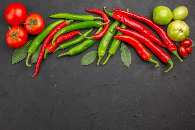 Bovenaanzicht hete rode en groene paprika's en tomaten laurierblaadjes op de top van zwarte grond met vrije ruimte