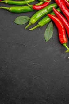 Bovenaanzicht hete rode en groene paprika's laurierblaadjes bovenaan zwarte tafel met vrije ruimte