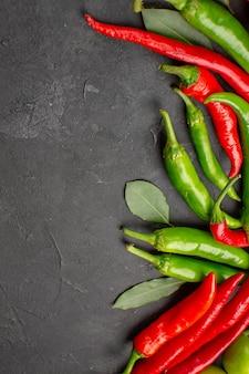 Bovenaanzicht hete rode en groene paprika's laurierblaadjes op zwarte grond met vrije ruimte