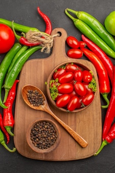 Bovenaanzicht hete rode en groene paprika tomaten kommen met kerstomaatjes en zwarte peper en lepel op een snijplank op zwarte grond