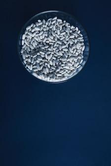 Bovenaanzicht hoop witte bonen in transparante glazen kom geïsoleerd op rustieke blauwe tafel. presentatie verkoopconcept n markt
