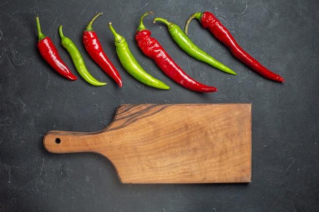 Bovenaanzicht horizontale rij groene en rode paprika's en snijplank op donkere ondergrond