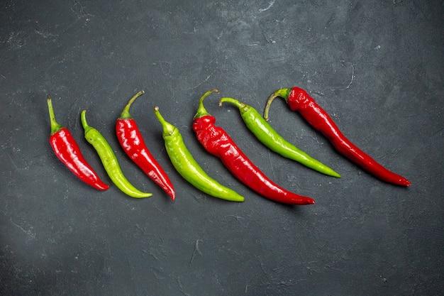 Bovenaanzicht horizontale rij groene en rode paprika's op donkere ondergrond met vrije plaats