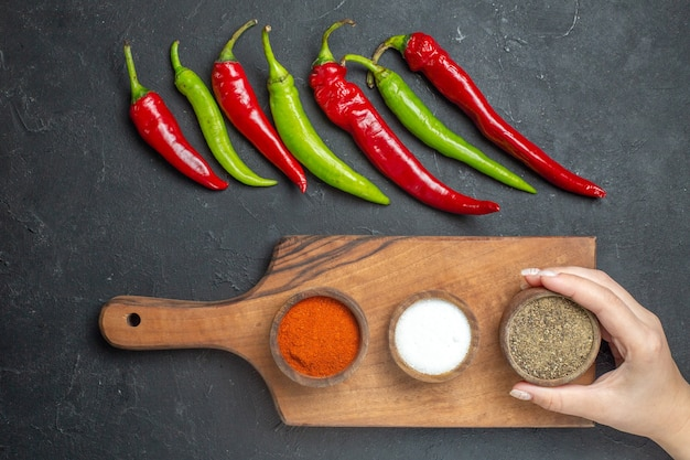 Bovenaanzicht horizontale rij groene en rode paprika verschillende kruiden op snijplank vrouwelijke hand op donkere ondergrond
