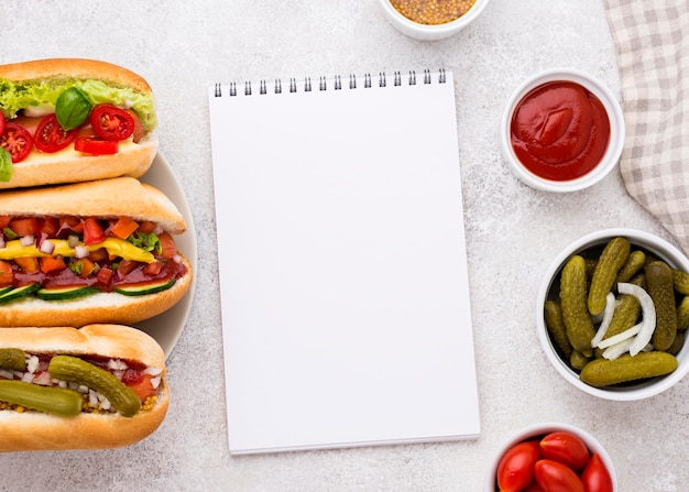 Bovenaanzicht hotdogs en notebook
