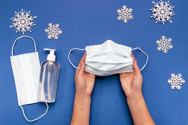 Bovenaanzicht houder van medisch masker in de buurt van sneeuwvlokken