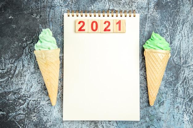 Bovenaanzicht houtblokken op notebook ijsjes op grijze achtergrond