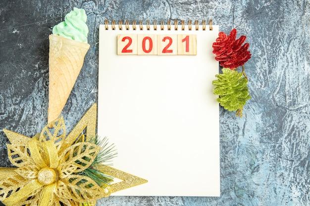 Bovenaanzicht houtblokken op notebook xmas ornamenten ijs op grijze achtergrond
