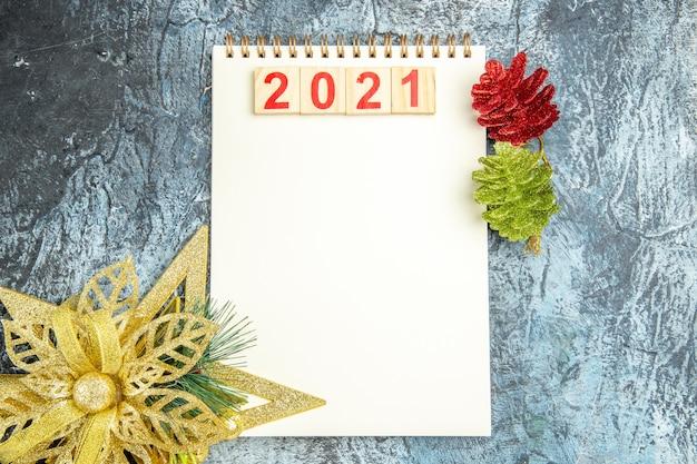 Bovenaanzicht houtblokken op notebook xmas ornamenten op grijze achtergrond