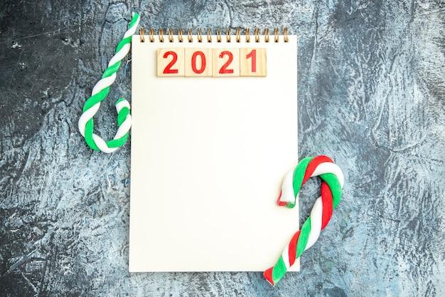 Bovenaanzicht houtblokken op notebook xmas snoepjes op grijze achtergrond