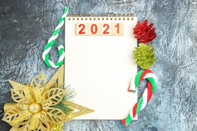Bovenaanzicht houtblokken op notitieboekje met kerstsnoepjes en ornamenten op grijze achtergrond