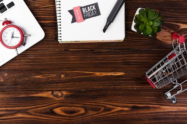 Bovenaanzicht houten bureau met zwarte vrijdag sticker op kladblok