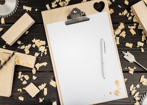 Bovenaanzicht houten gereedschap op bureau met klembord