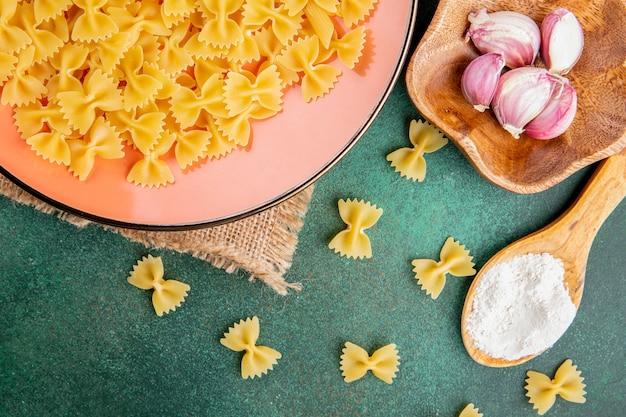 Bovenaanzicht houten lepel met bloem met rauwe pasta in een bord met knoflook op een groene tafel