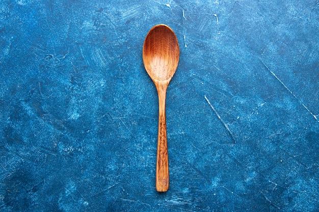 Bovenaanzicht houten lepel op blauwe tafel kopie plaats