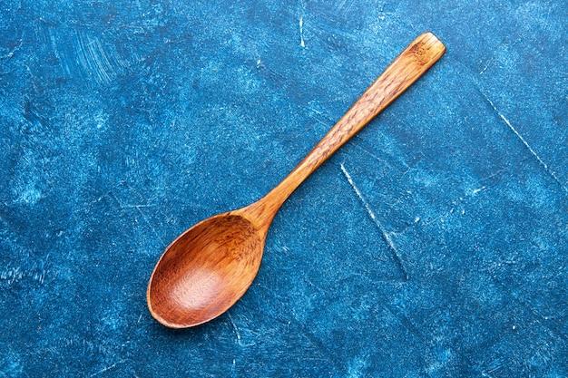 Bovenaanzicht houten lepel op blauwe tafel met kopie plaats