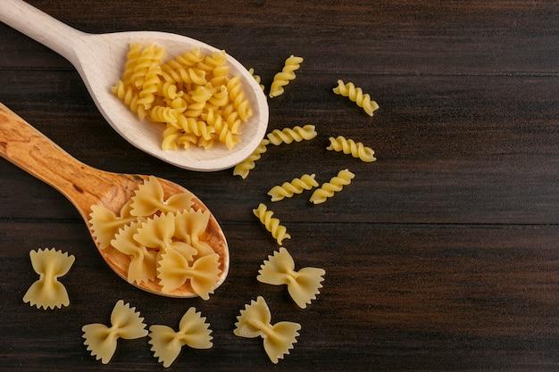 Bovenaanzicht houten lepels met rauwe pasta op een houten tafel