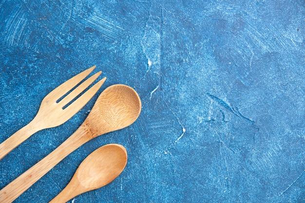 Bovenaanzicht houten mes vork lepel op blauwe tafel vrije plaats