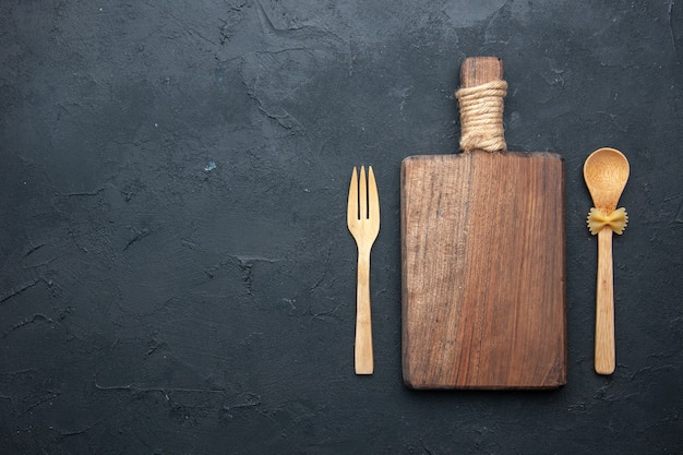 Bovenaanzicht houten serveerplank houten lepel en vork op donkere tafel kopie plaats