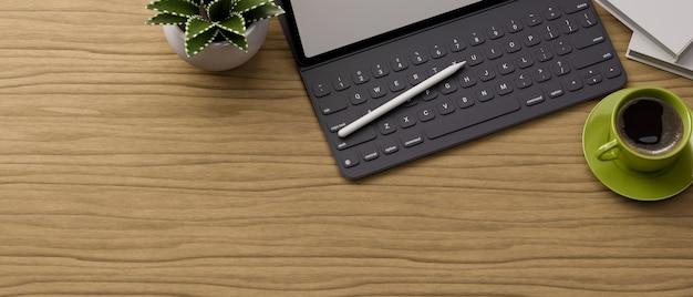 Bovenaanzicht houten tafel met digitale tablet toetsenbord stylus pen beker plant pot