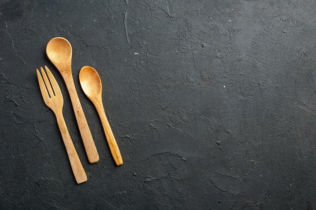 Bovenaanzicht houten vork en lepels op donkere tafel met vrije plaats