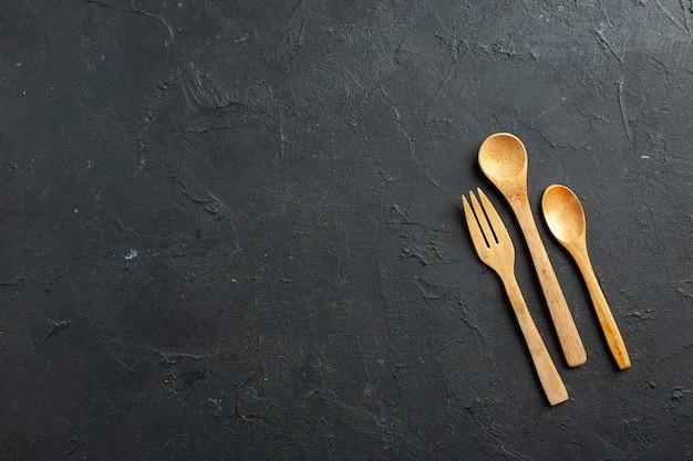 Bovenaanzicht houten vork en lepels op donkere tafel met vrije ruimte