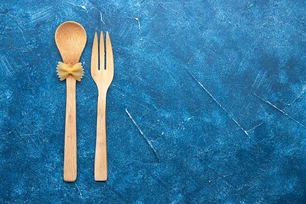 Bovenaanzicht houten vork lepel farfalle op lepel op blauwe tafel met vrije ruimte