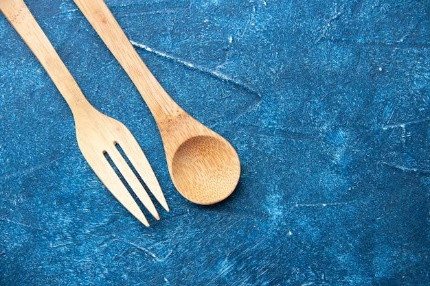 Bovenaanzicht houten vork lepel op blauwe tafel vrije plaats
