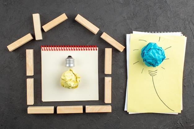 Bovenaanzicht huis vormige houtblokken doelen geschreven op kladblok ideagloeilamp op papier op zwart