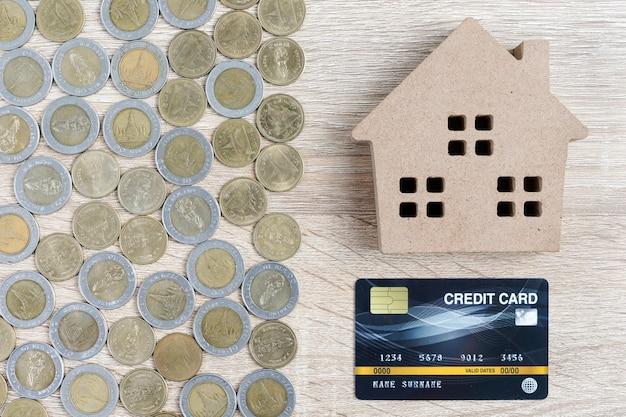 Bovenaanzicht huismodel en munten met creditcard op houten tafel gebruiken als onroerend goed en financieel concept