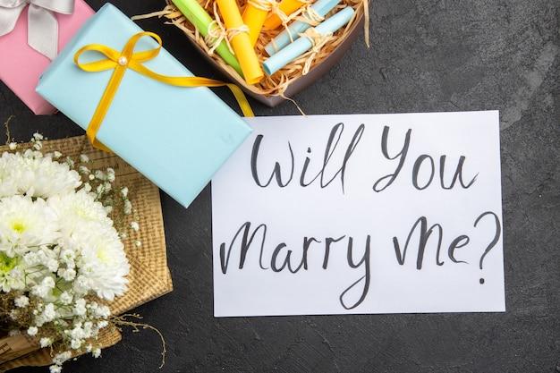 Bovenaanzicht huwelijksaanzoek concept cadeau bloemboeket wil je met me trouwen geschreven op papier scroll wenspapieren in doos op donkere achtergrond