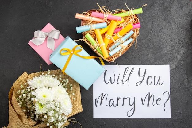 Bovenaanzicht huwelijksaanzoek concept geschenk bloemboeket wil je met me trouwen geschreven op papier scroll wenspapieren in doos op tafel
