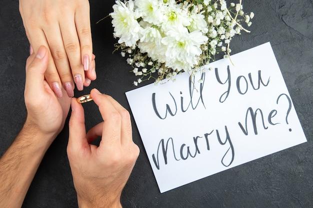 Bovenaanzicht huwelijksaanzoek concept man handen plaatsen ring op vrouw hand bloemen wil je met me trouwen geschreven op papier op donkere achtergrond