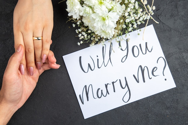 Bovenaanzicht huwelijksaanzoek concept mannelijke hand met vrouwelijke hand met ring bloemen wil je met me trouwen geschreven op papier op donkere achtergrond
