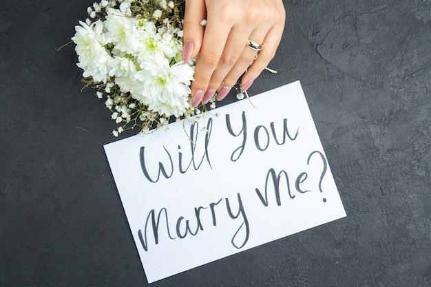 Bovenaanzicht huwelijksaanzoek concept vrouwelijke hand met ring bloemen wil je met me trouwen geschreven op papier op donkere achtergrond