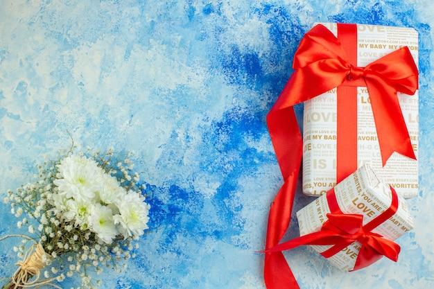 Bovenaanzicht huwelijksgeschenken met rode linten witte bruiloft bloemen op blauwe achtergrond kopie plaats