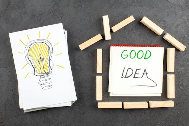 Bovenaanzicht ideagloeilamp op papieren huisvormige houtblokken goed idee geschreven op notitieboekje op zwart