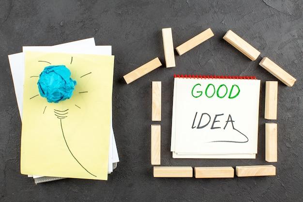 Bovenaanzicht ideagloeilamp op papieren huisvormige houtblokken goed idee geschreven op notitieboekje op zwarte tafel