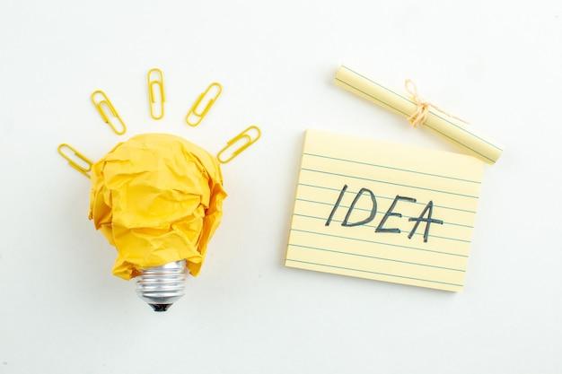 Bovenaanzicht idealight bulb gem clips idee geschreven op notitie op wit