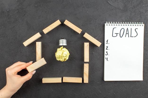 Bovenaanzicht idealight lamp in huis vormige houtblokken doelen geschreven op notitieblok houtblok in vrouwelijke hand op zwart