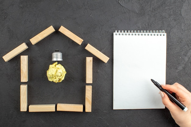 Bovenaanzicht idealight lamp in huis vormige houtblokken notitieblok zwarte stift in vrouwelijke hand op zwart